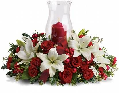 It's beginning to look a lot like Christmas! Add a warm glow to your holiday décor with this lush arrangement of red roses and carnations. A beautiful Christmas centerpiece with its classic glass hurricane and red pillar candle, it also looks lovely on a mantle or entry table.