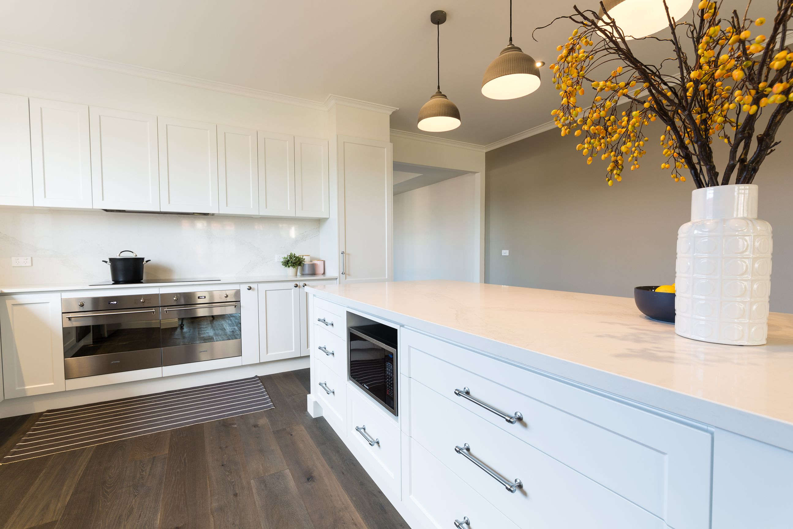 White Shaker Style Vinyl Wrap Kitchen With Stone Bench Tops And Splash Back