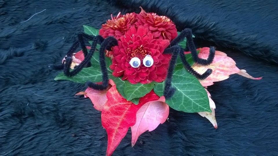 Scary spider made with chrysanthemums, leaves and pipecleaners