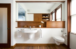 """""""Whenever you're making a minimal bathroom, you always have issues with storage,"""" Klug says. The wall-hung Duravitsink leaves no place """"to put all your junk,"""" so Klug and Butz added small shelf above. The space to the right, which appears as an extension of the shelf is actually a panel that hides access to the water tank of the wall-hung toilet, also by Duravit.Photo by <br><br>Eric Roth"""