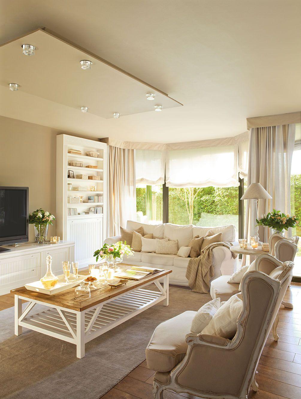 Salón con mobiliario en blanco y en tonos tierra con dobles cortinas ...