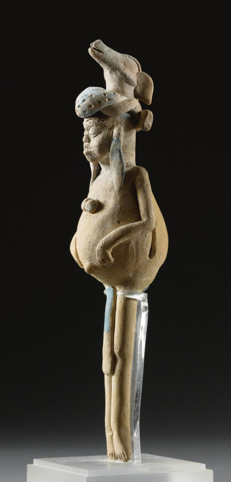 A MAYA FIGURAL RATTLE, JAINA,  LATE CLASSIC, CA. A.D. 550-950   depicting a dwarf with distinctive bloated torso, containing tiny pellets as rattle, with attenuated straight legs, the round cheeked face with eyes lowered to a crescent, and wearing a thick twisted turban and deer as headdress, long cloth earrings and meager loincloth tied around the hips, areas of Maya blue pigment.  height 7 1/2 in. 19 cm