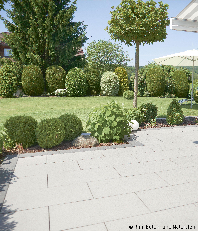 Eine Terrasse mit Blick ins Grüne. Die Rasenfläche wird abgegrenzt von einem kleinen Beet, hier finden sich auch wieder runde Formen und Sträucher, die sich auch im Garten an anderen Stellen wiederfinden lassen. Eine Mähkante, die gut aussieht und eine Terrassenplatte, die Wohlfühlcharakter hat. #rinnbeton #design #gartengestaltung #modernlandscapedesign