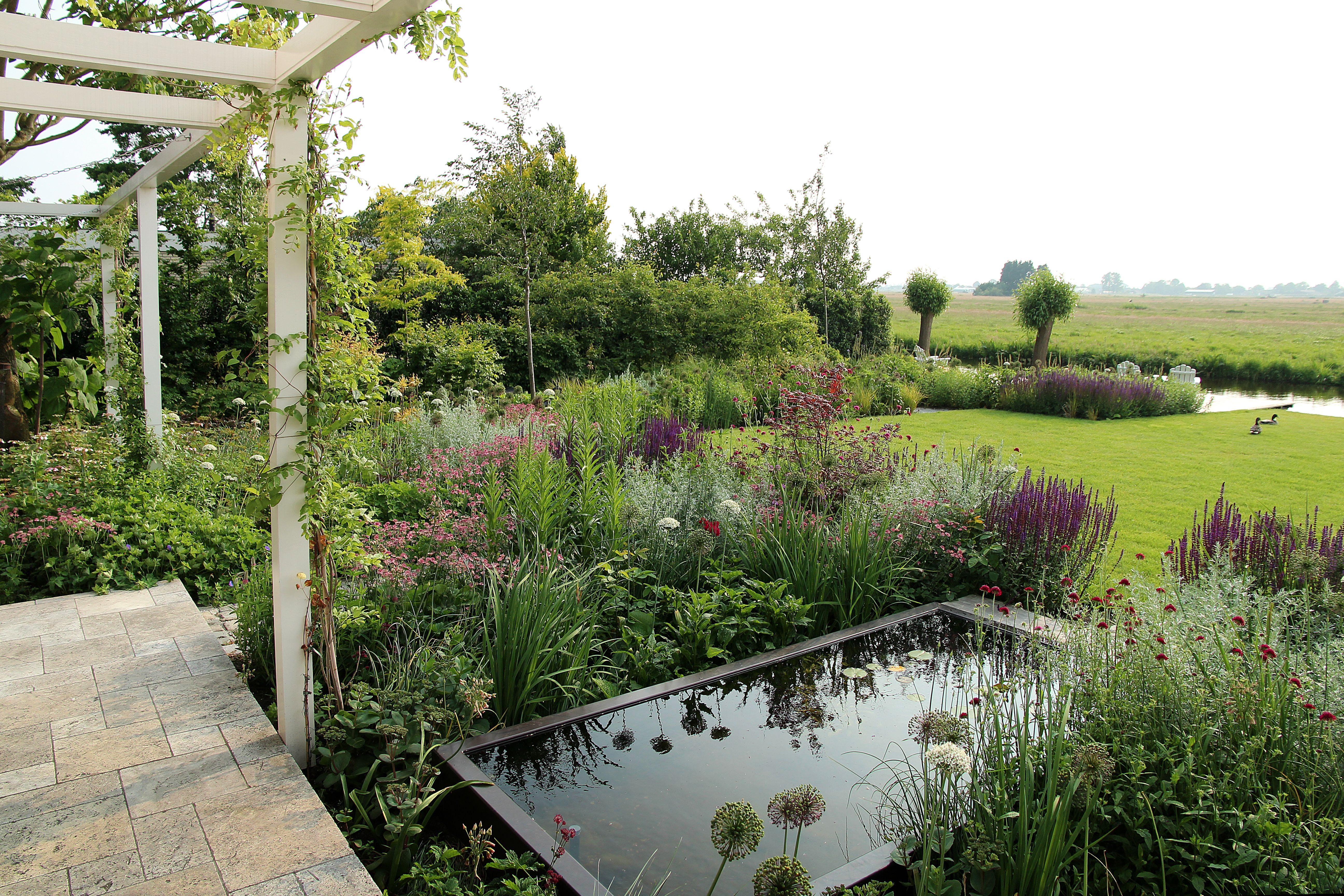 Weelderige landelijke tuin met witte pergola en een for Huis in de tuin