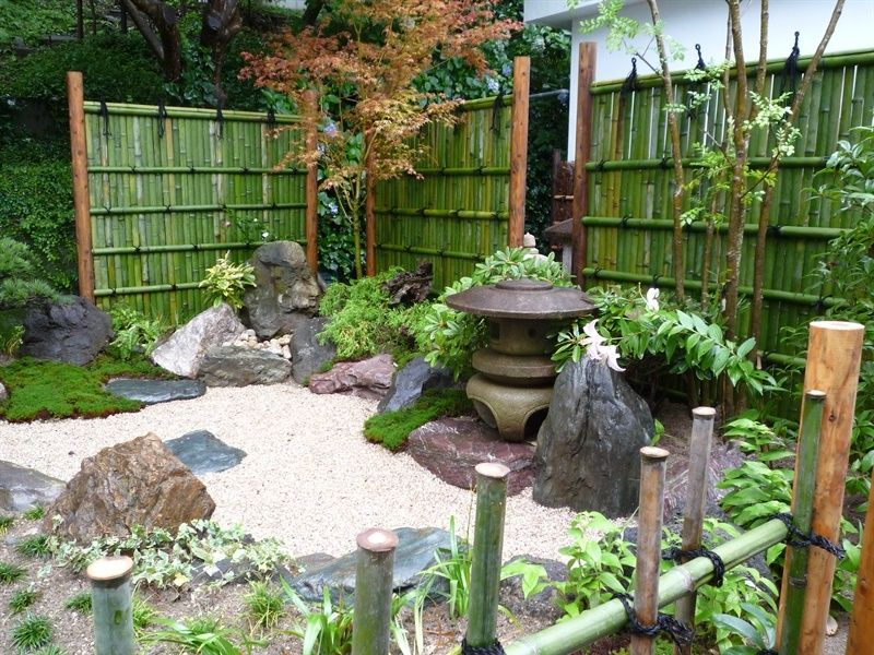 japanese garden design beautiful with stone lamp place with white small crushed stone and big stone with bamboo fence and trees with plants patio