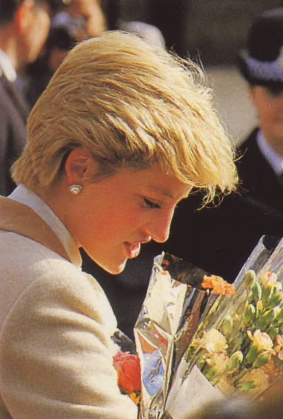 Princess Diana, 1986 look maybe. Wearing a beige jacket with tan trim, cream blouse, pearl earrings.