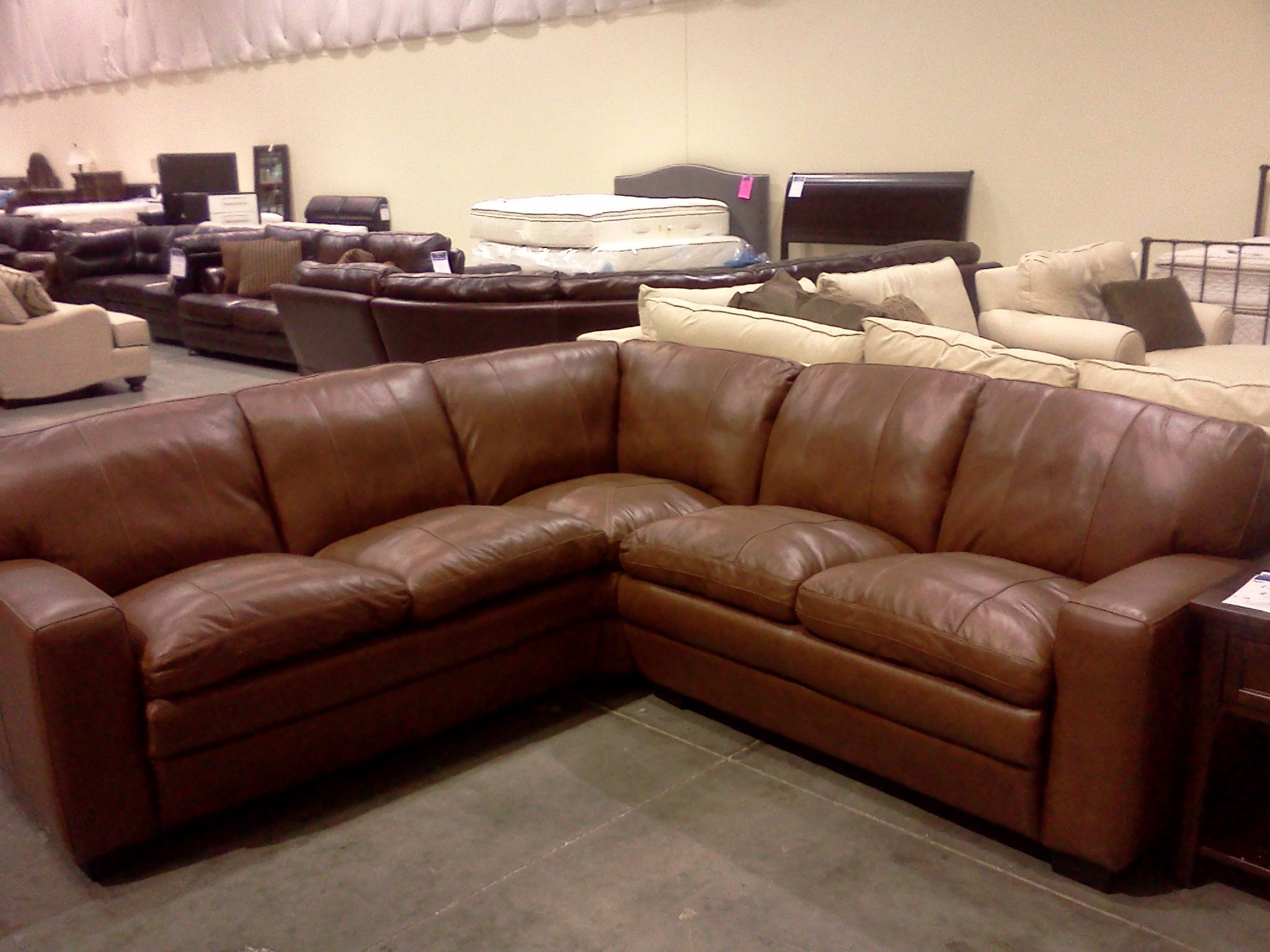 Baseball glove fit on this brown leather plush seat sectional In