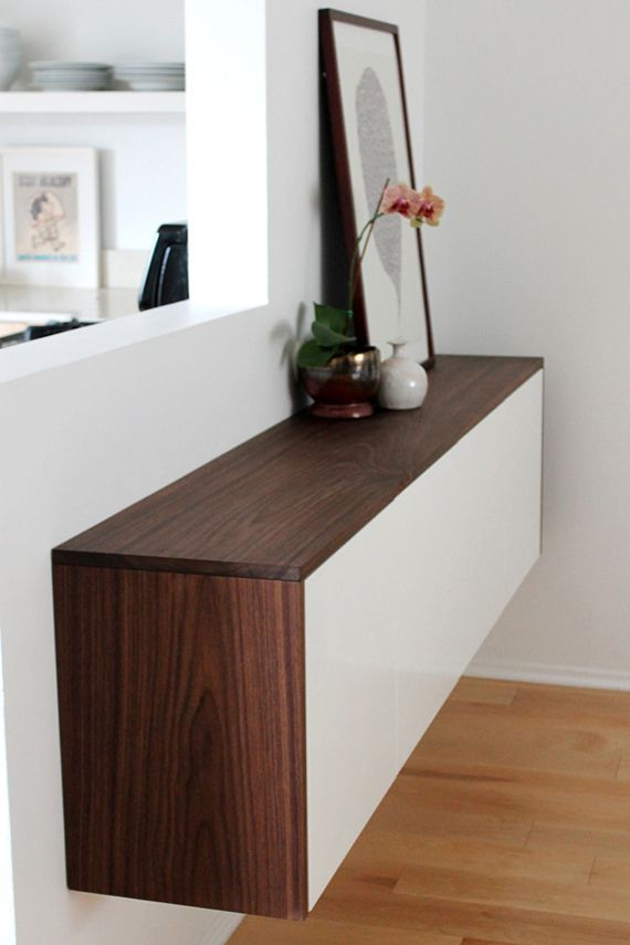 Mount two Ikea Akurum kitchen cabinets next to each other on a wall to make your own credenza. To create a two-toned contrasting long wall credenza, you can surround the cabinets with a dark shade of stained wood. This DIY credenza is perfect for storing your dining are essentials for a less cluttered room.
