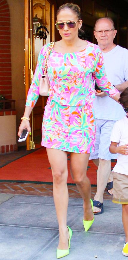 Jennifer Lopez is not one to shy away from making a statement! She styled her bright floral print dress with a pale pink purse, a chunky gold chain bracelet, and blindingly neon pumps.