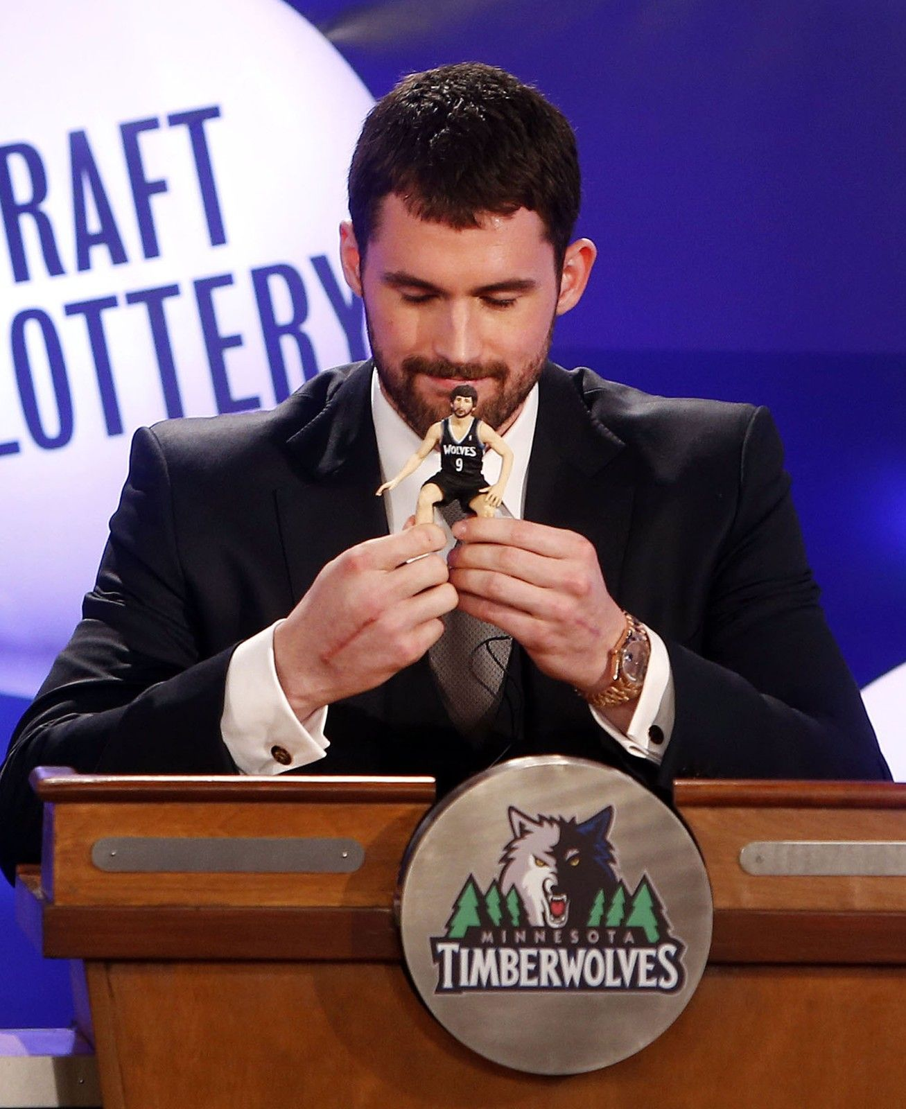 Kevin Love holds a Ricky Rubio bobble head doll he brought for good luck during the NBA basketball draft lottery, Tuesday, May 21, 2013 in New York.