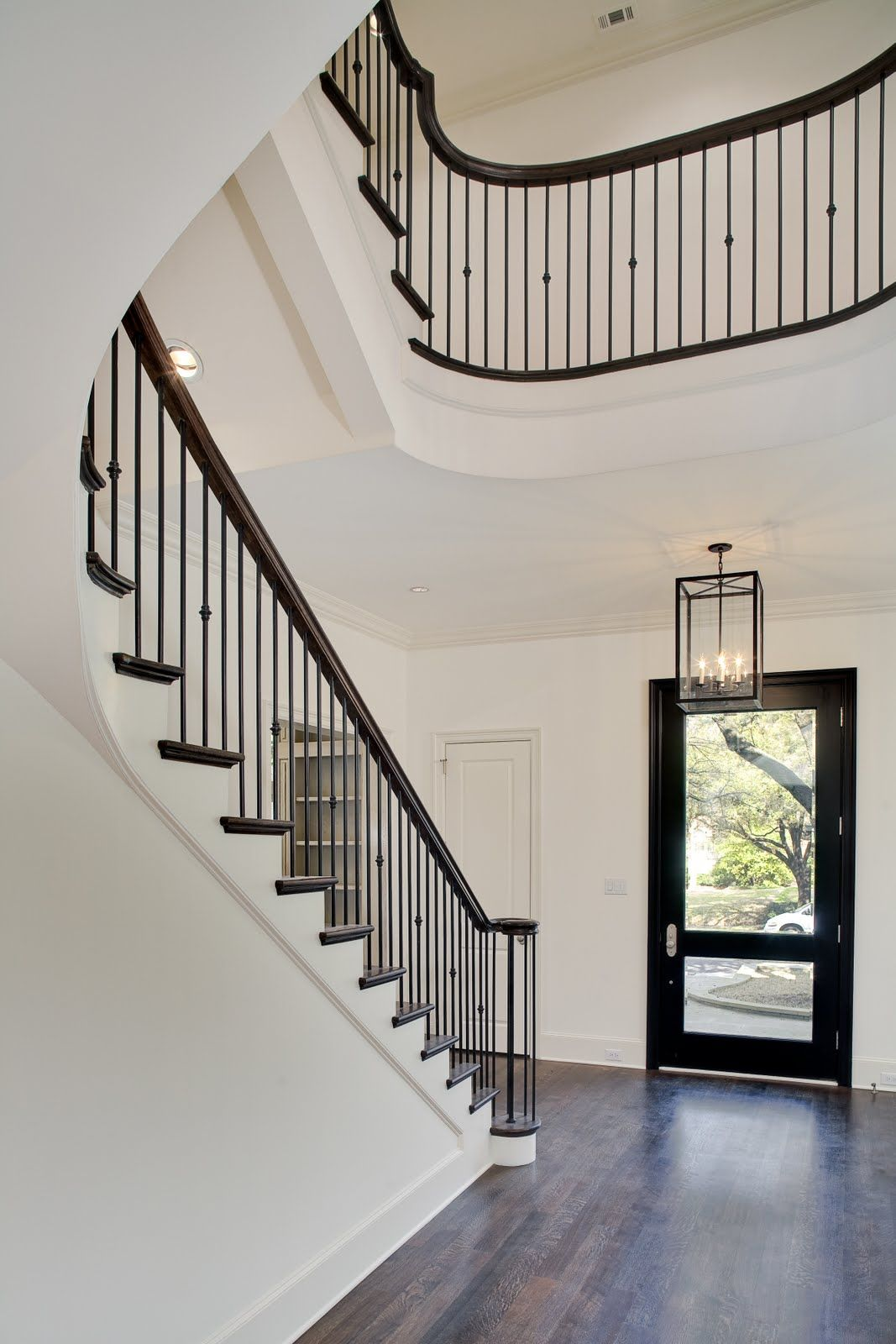 Dark Bannister With Iron Pegs And Hardwood Floors