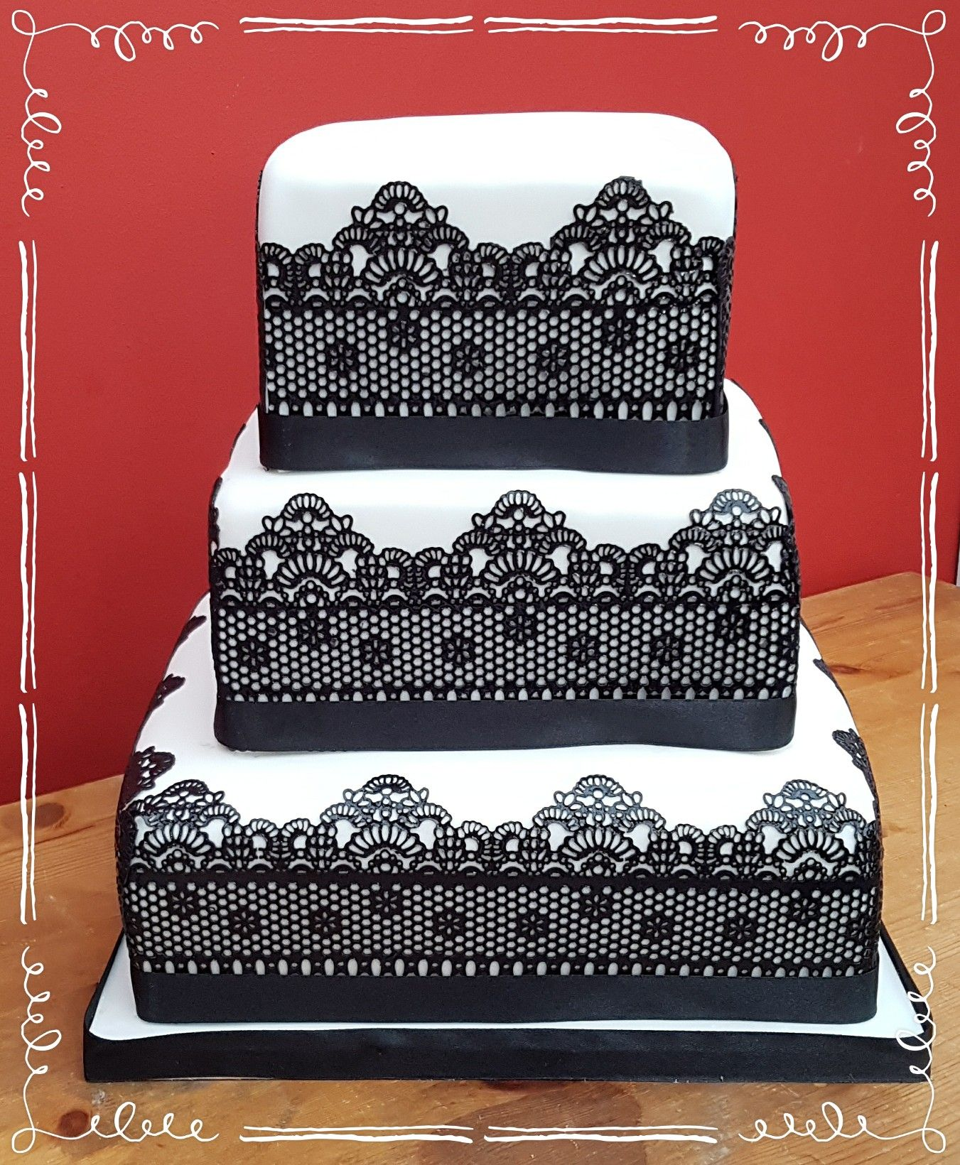 Black and white tier square wedding cake with black lace detail