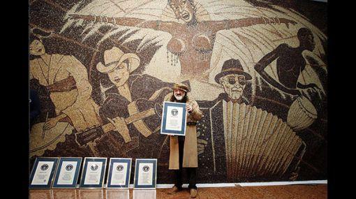 """Mosaico titulado """"Un mundo, una familia, un café"""". Artista albanés """"Saimir Strati"""".   Obra que le hace lograr su sexto ingreso al libro de los Récord Guinness en el año 2011, realizado con 1 millón de granos de café, con una medida de unos 25 m2 y un peso de unos 170 kgs.  Para dibujar todas estas figuras, el maestro utilizó granos de café no procesados, cocidos y medio cocidos, lo que le dan un toque de diferentes colores."""