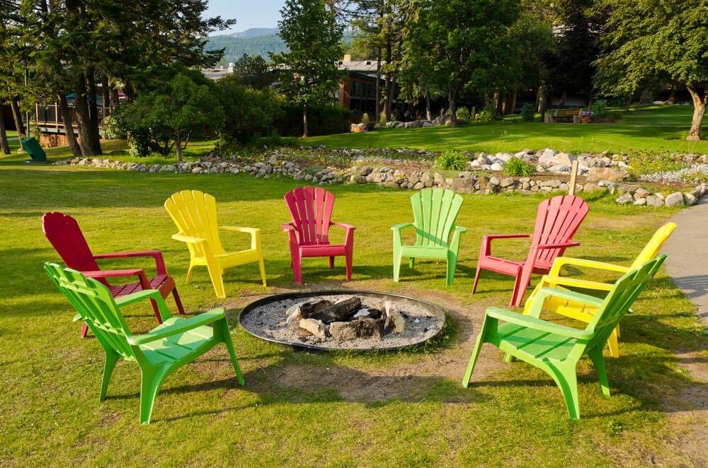 In Runde Feuerstelle Mit Sand Auf Rasenfläche Umgeben Von Bunten Adirondack  Stühle Gegraben.