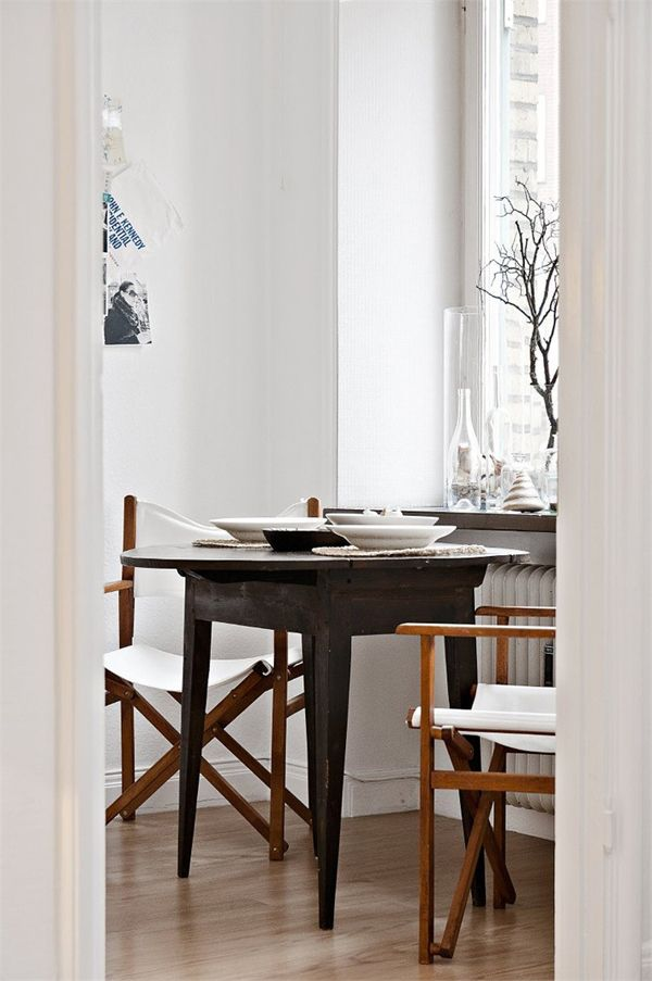 kitchen corner with small wood dining table and two white camp