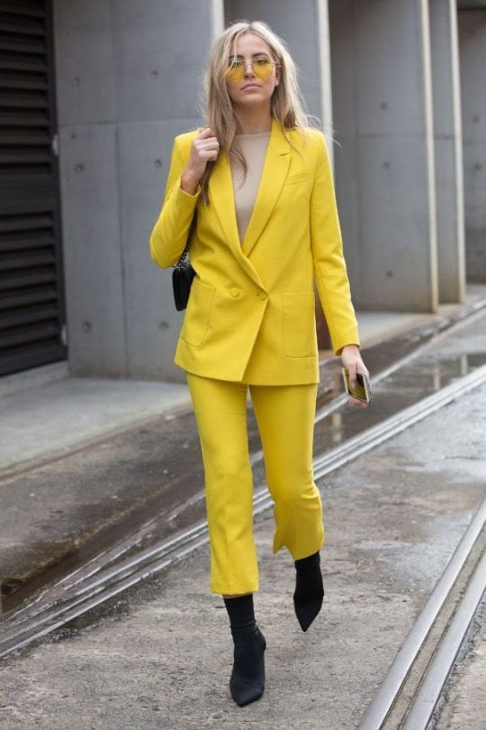 A Neon Yellow Pantsuit A Neutral Top And Black Sock Boots