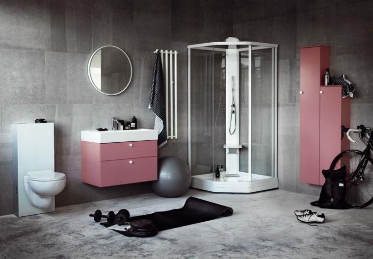 Bagno con piastrelle di colore grigio e mobili rosa box doccia con
