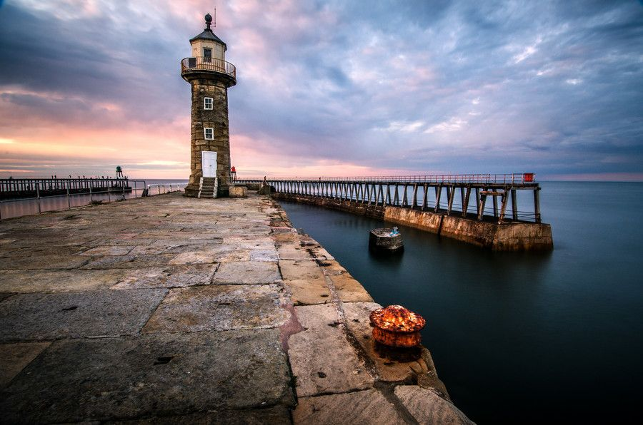 The sun sets over the Pier and Lighthouse at Whitby, North Yorkshire