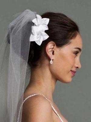 Modèle de coiffure de mariage avec une fleur blanche attachée sur le côté  avec un petit voile attaché sur un chignon haut. Coupe de cheveux de mariage  sur