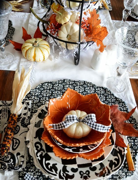 patterned black and white chargers, pumpkins with a black and white - halloween table setting ideas