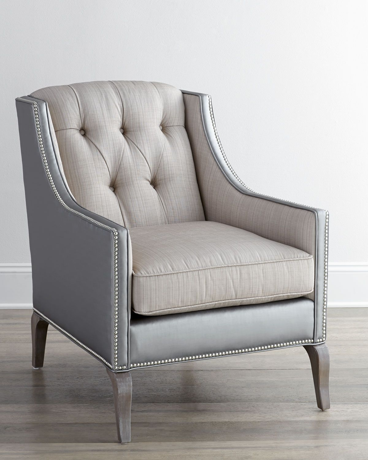 Chair features narrow arms and buttontufted back