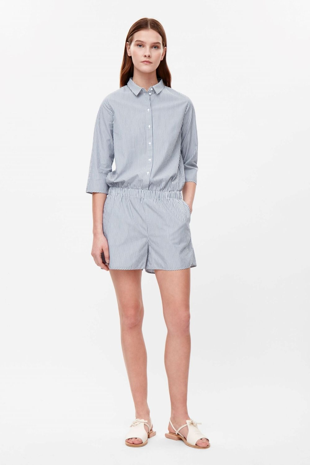 This shirt inspired jumpsuit is made from a soft cotton with an all-over stripe pattern. A relaxed fit and a short style, it has a neat collar, 3/4 sleeves and subtle side seam pockets.
