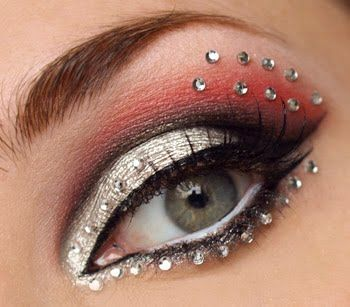 Striking silver  red eye make-up accented by crystals.