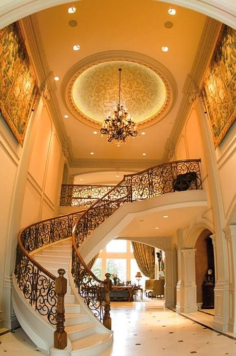 Grand staircase in foyer leading to grand double story great room ...