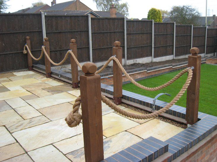 Some rope fencing decorating the edge of a patio garden for Garden decking fencing