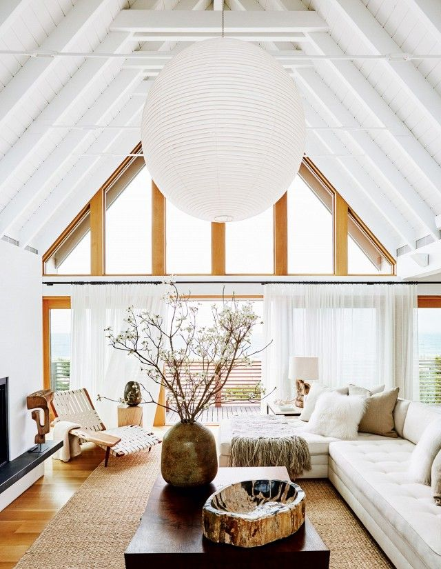 Bright Living Space With Wooden Beams A Large Paper Lantern And White Sectional