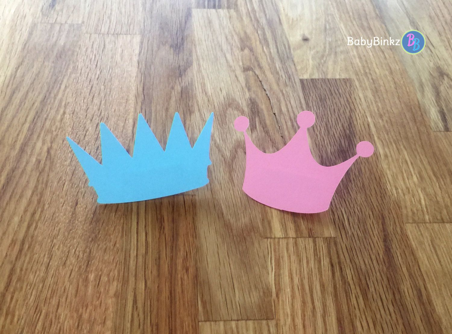 Planning a Gender Reveal Baby Shower? Our Gender Reveal Party Pins will be the perfect addition! Choose your side! Is it a Little Prince or A Little Princess? Let your guests vote for the gender by selecting a Tiara or Crown pin when they arrive!  Each set includes 6 x 3 die cut blue crowns and 6 x 2.5 die cut pink tiaras created out of heavy weight card stock with a mounted bar pin. All 12 of your pins come fully assembled & ready to use!   Need more than 12? You can add additional sets ...