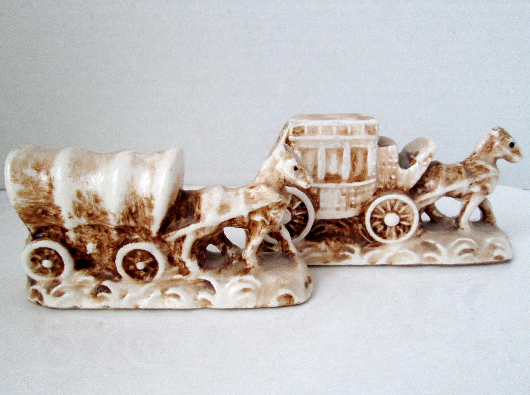 "This is a lovely set of Old West salt and pepper shakers of a horse drawn covered wagon and a horse drawn stagecoach. The base is glazed white and has brown ""antiquing"" hand painted on them. Both have"