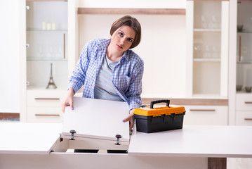Young beautiful woman assembling furniture at home , #ad, #woman, #beautiful, #Young, #home, #furniture #Ad
