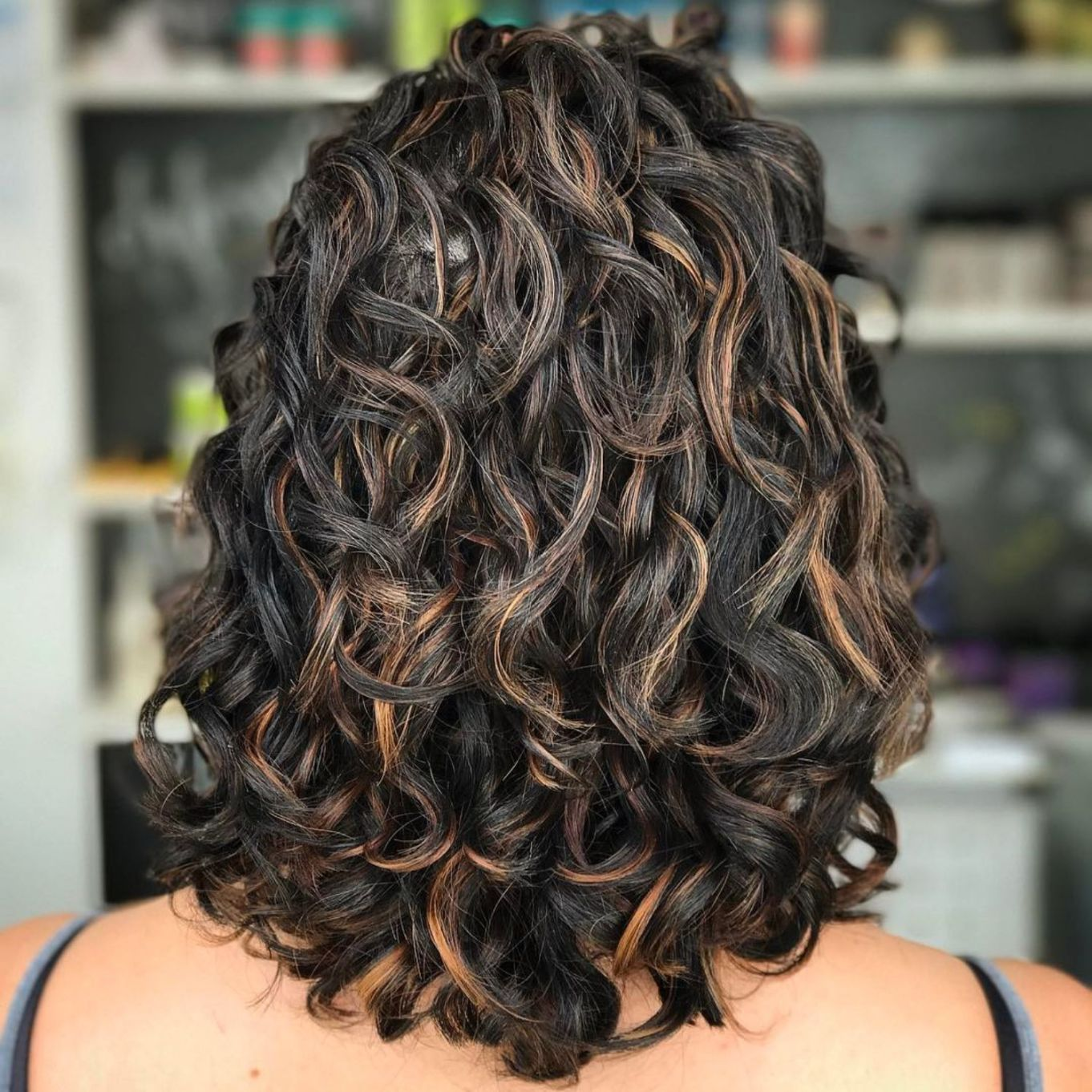 Black curly hairstyle with copper highlights in 2020