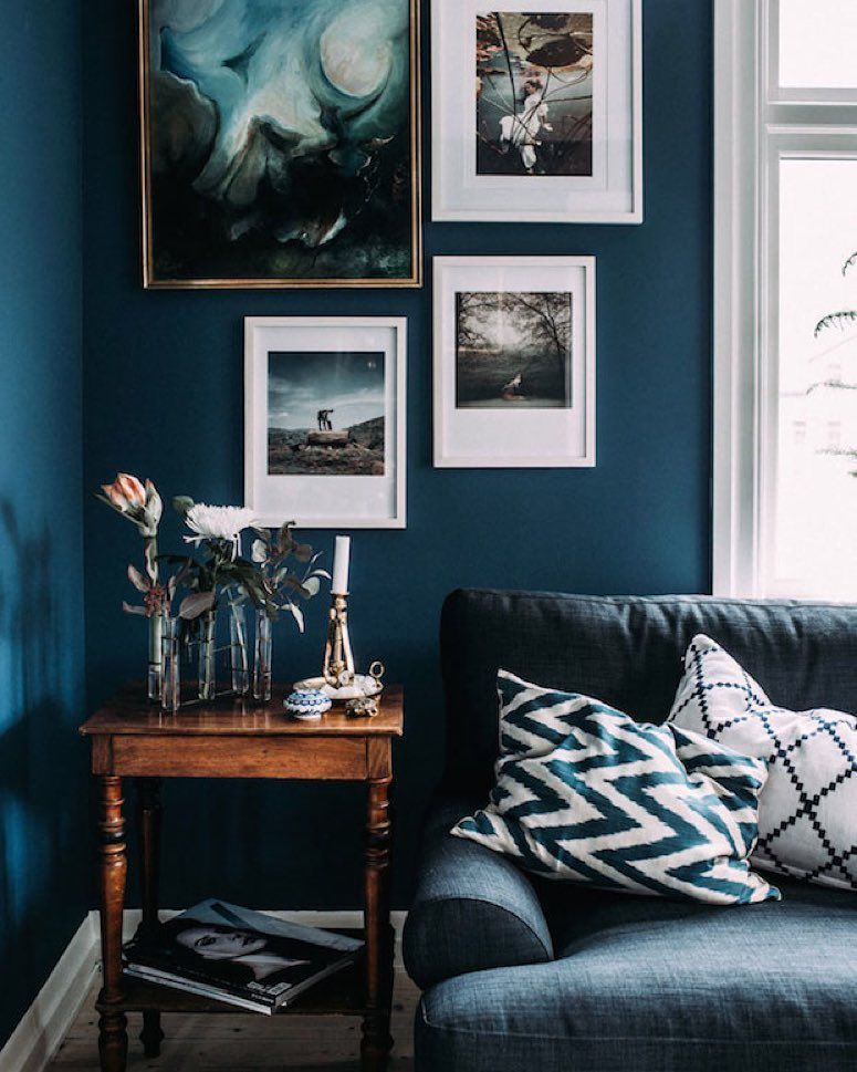 Loving the dark blue accents and art in the Swedish home of