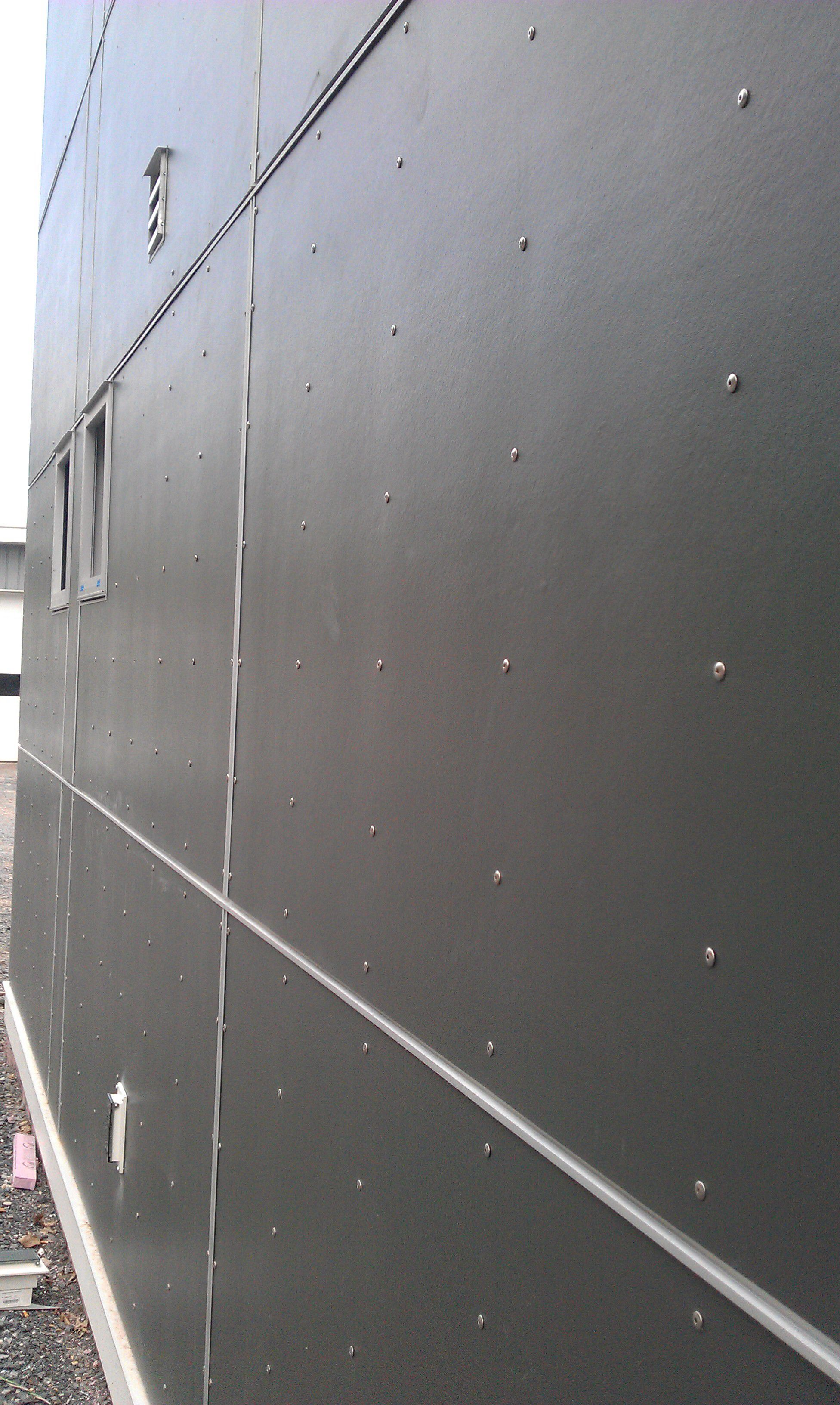 James Hardie Panels In Dark Grey With Exposed Fastening Screws To Give A Rivet Look Exterior Wall Materials Exterior Cladding Modern Exterior