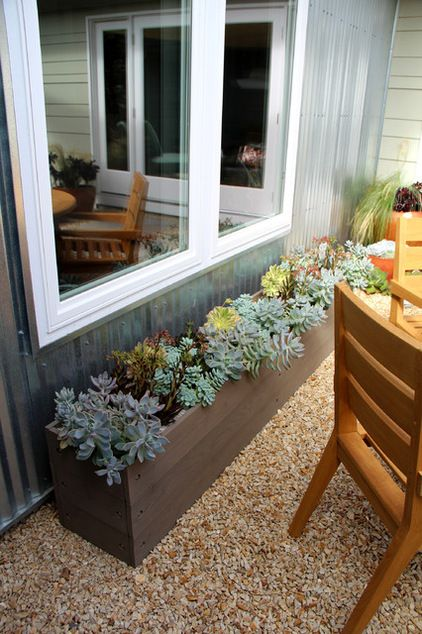 A Long Planter Filled With Succulents Under The Eaves Has
