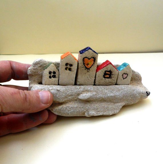 Miniature ceramic houses on a beach stone, one of