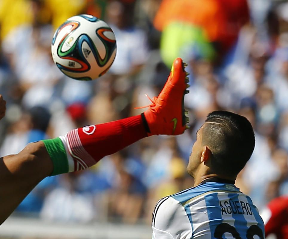 Iran's Mehrdad Pouladi (L) fights for the ball with Argentina's Sergio Aguero during their 2014 World Cup Group F soccer match at the Mineirao stadium in Belo Horizonte June 21, 2014.