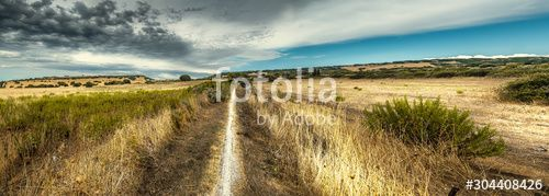 Panoramic view of a dirt path under a cloudy sky
