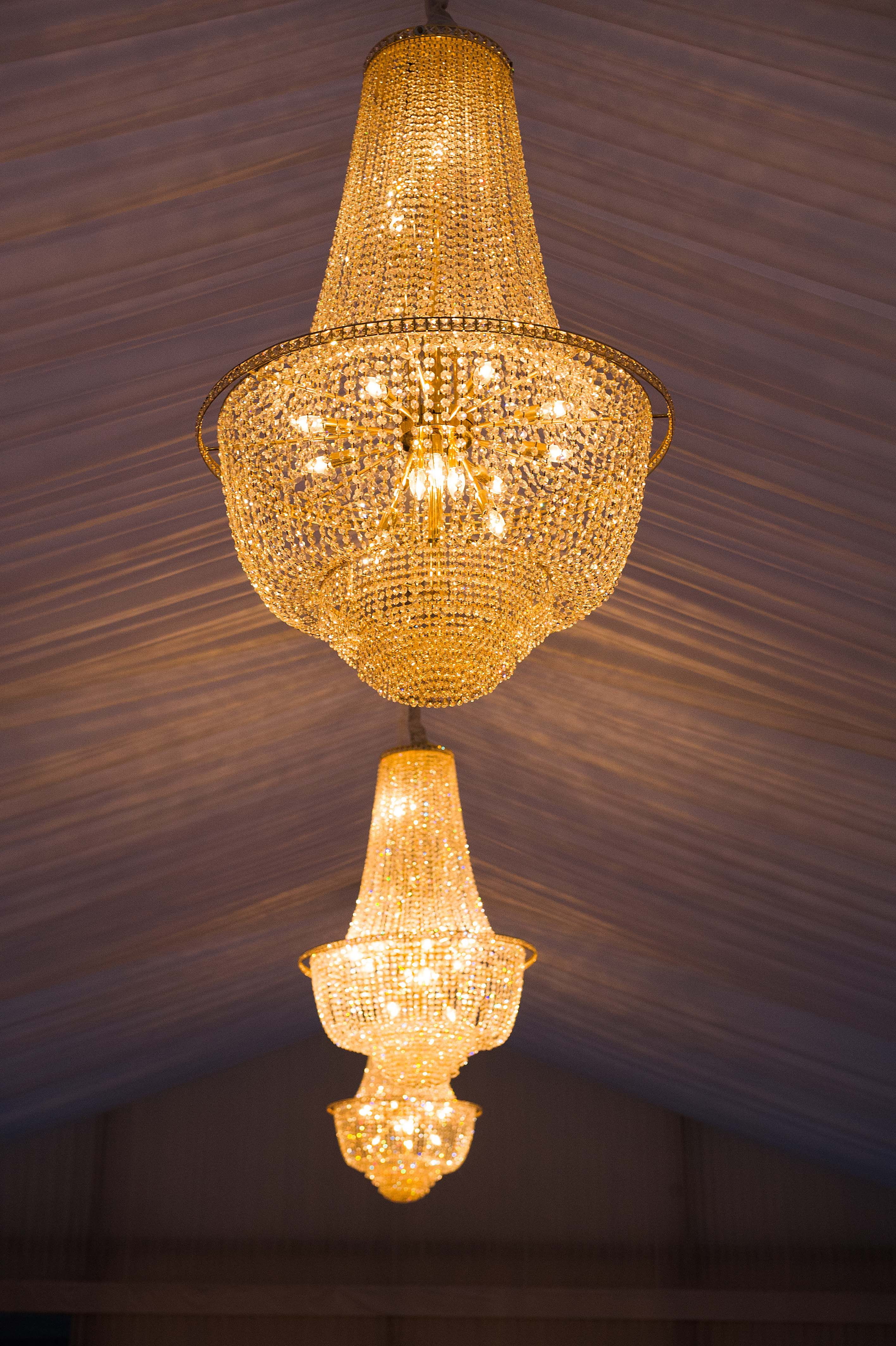Crystal chandeliers in pleated tack off lined marquee