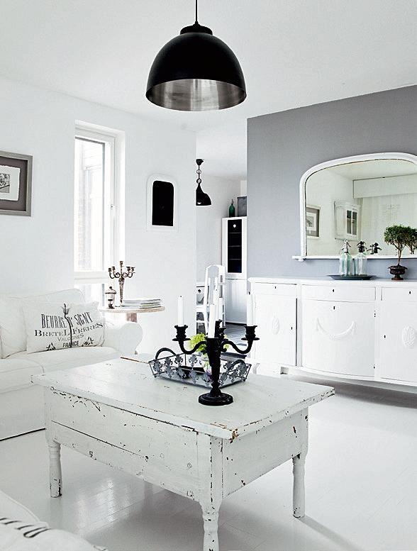 Yksi olohuoneen seinä on maalattu harmaaksi. Valaisin ja muutama muu musta yksityiskohta tuovat ryhtiä muuten valkoiseen kotiin. | Tyyli vaihtoon | Koti ja keittiö | Jonna Kivilahti | Kuva Krista Keltanen