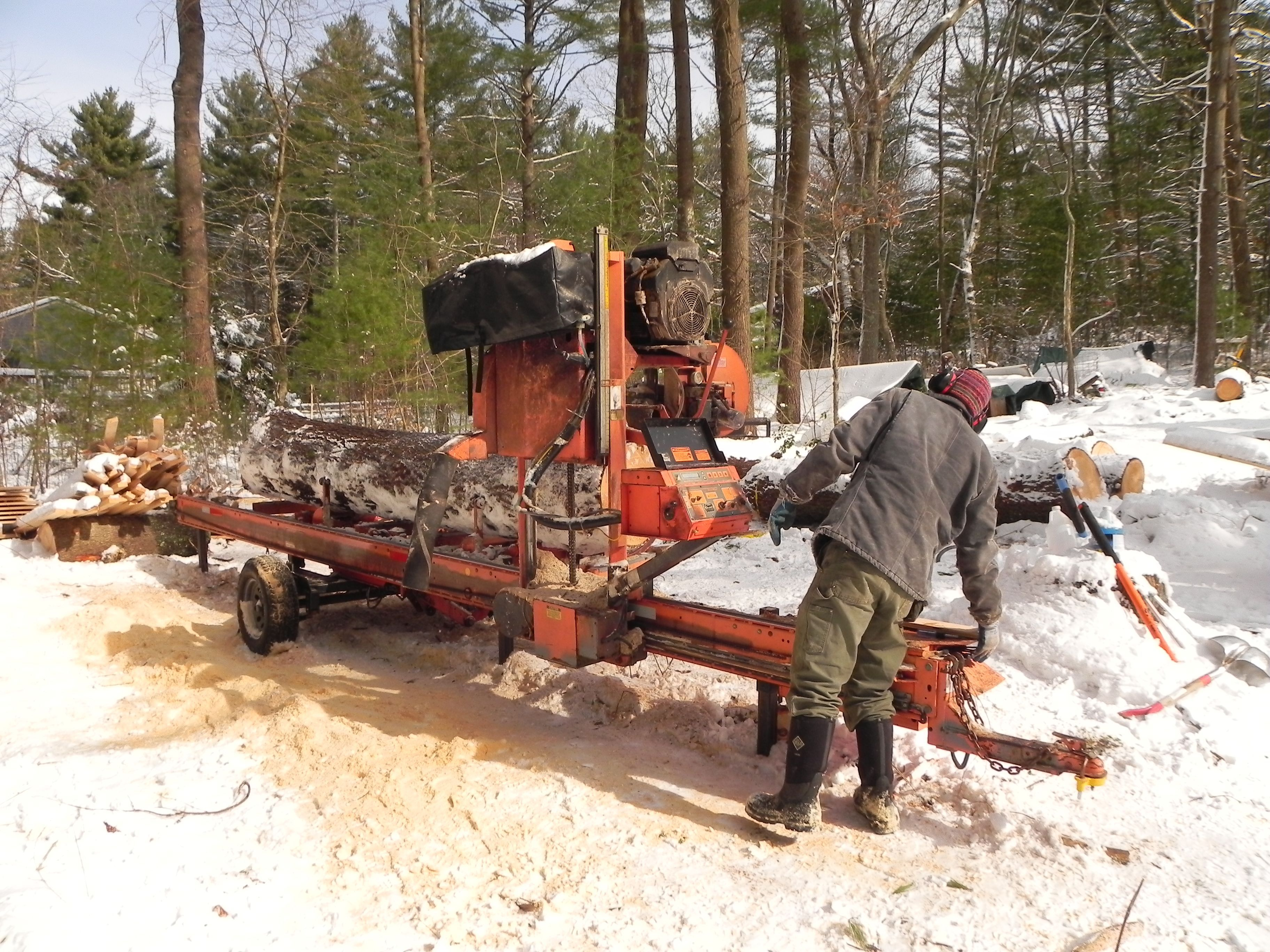 Portable sawmill at work in the snow.