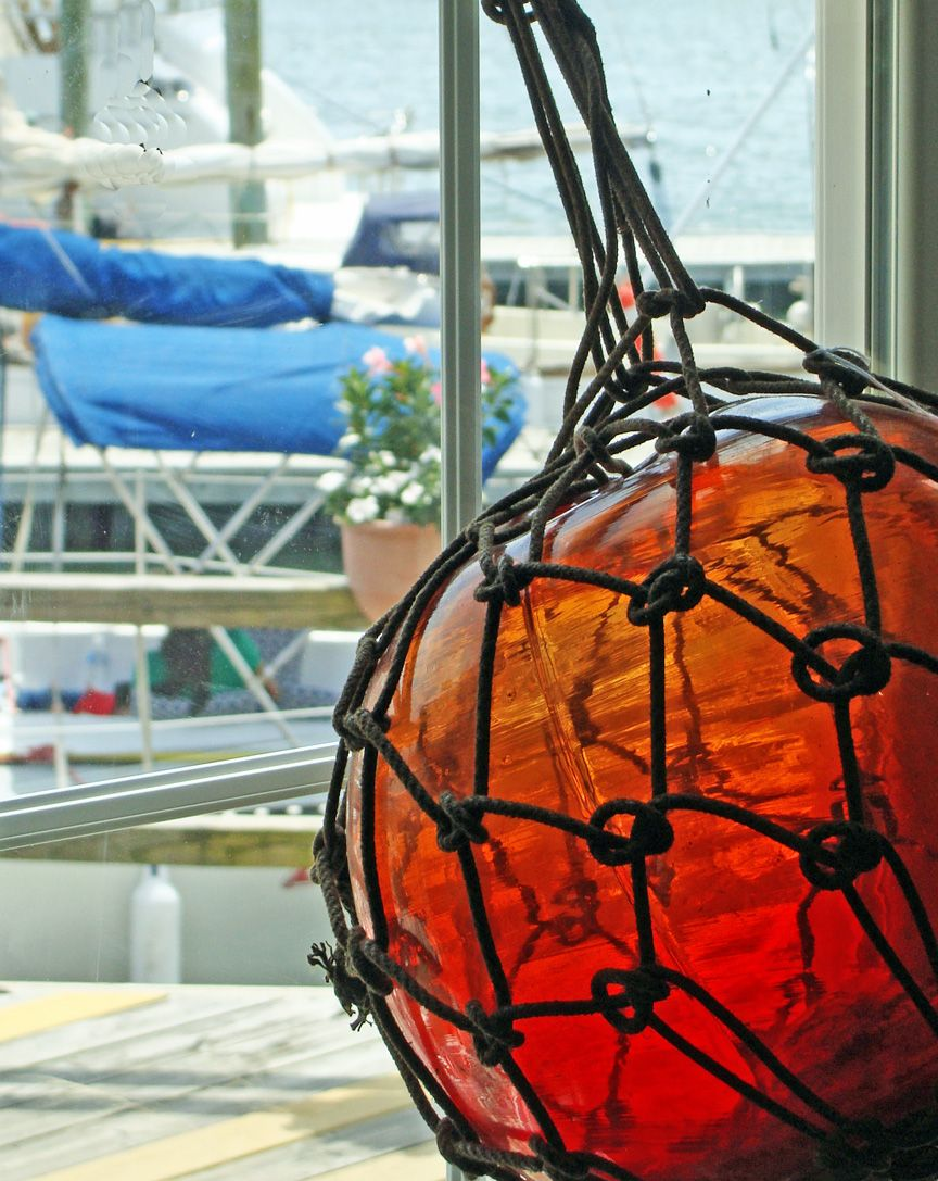 A blown glass float ball with hand-tied netting adds bright orangy ...