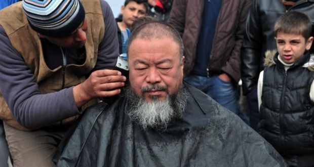 Chinese artist and activist Ai Weiwei gets a shave at the makeshift Greek camp at Idomeni. Photograph: Sakis Mitrolidis/AFP/Getty Images