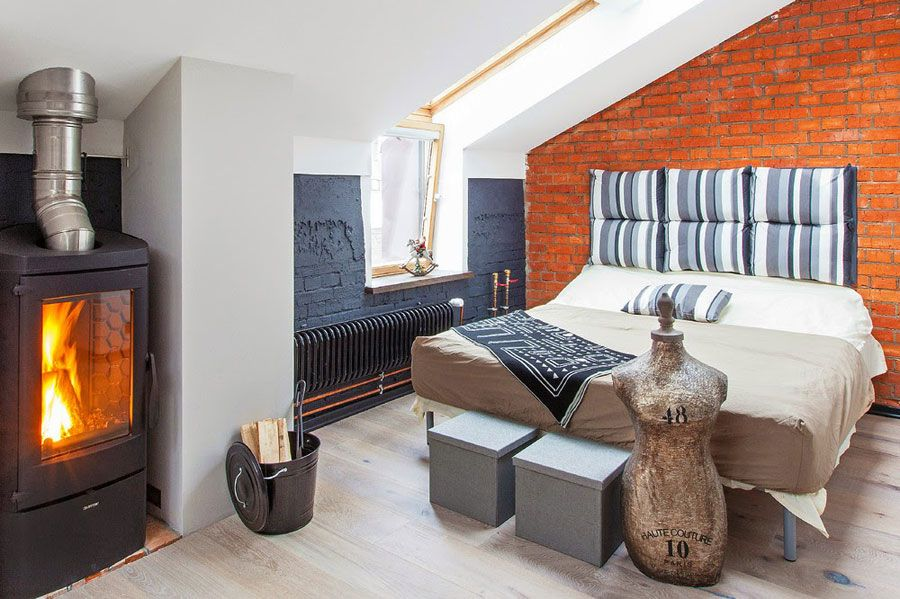 small loft bedroom with red brick wall and fireplace