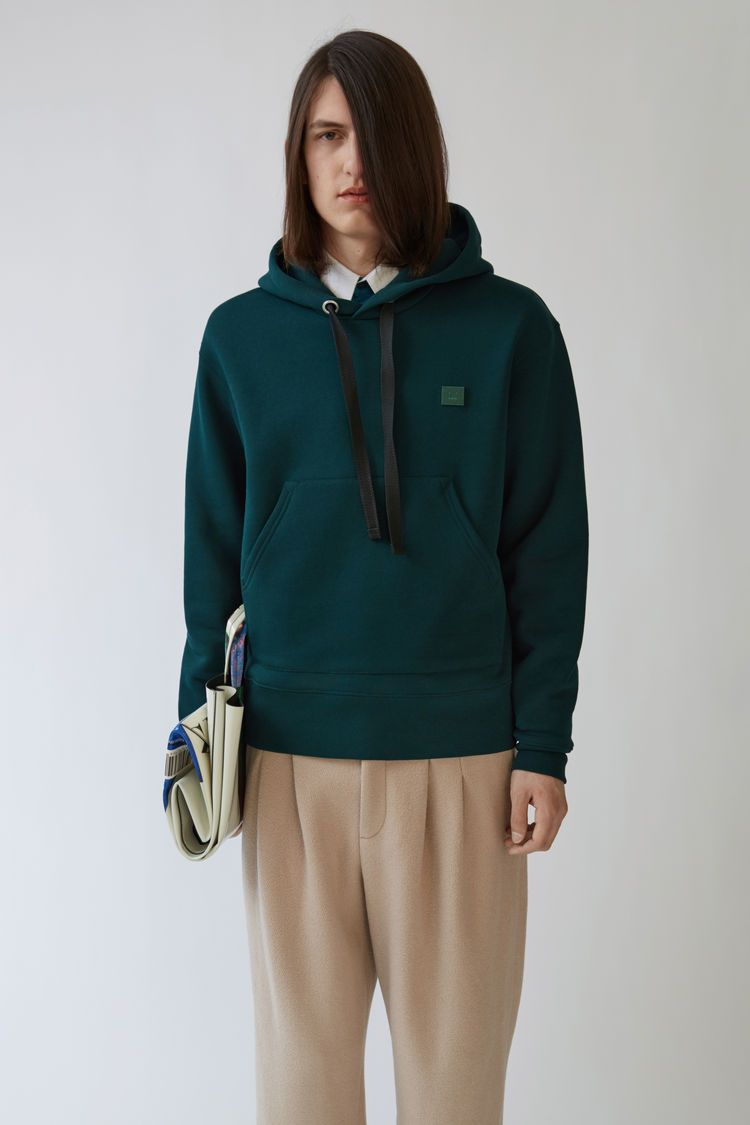 Acne Studios Ferris Face bottle green is a regular fit hooded sweatshirt  with an embroidered face bb734793253