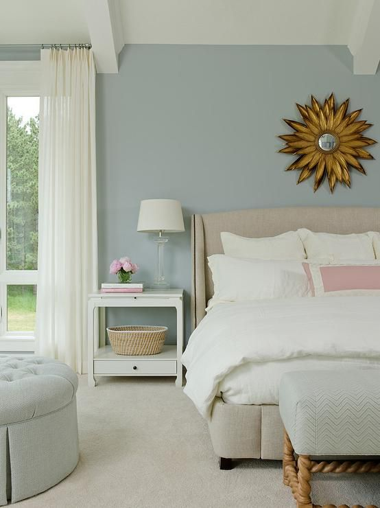 Blue Bedroom Features A Gold Sunburst Mirror Over A Wingback Bed