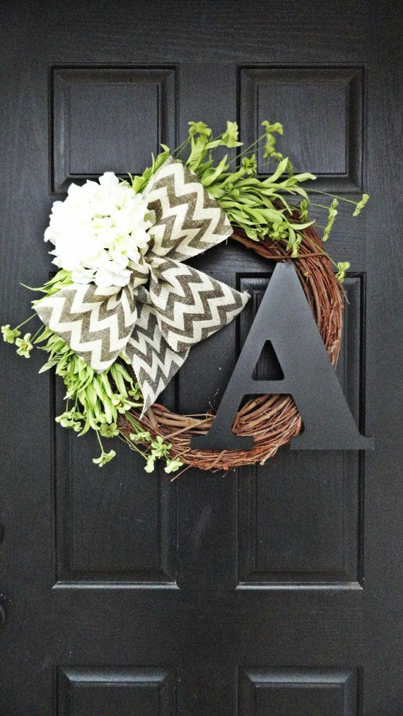 This wreath makes such a lovely statement of vibrancy and rustic charm. Gray and off white chevron perfectly sets of the pretty bright white hydrangea and vibrant green wildflowers. A very large 12 black monogram adds just the right amount of personal charm. Wreath measure approximately 20 in diameter including florals and decorations. Mounted on 18 grapevine wreath base. Choose a letter and bow color by way of pull down menu.