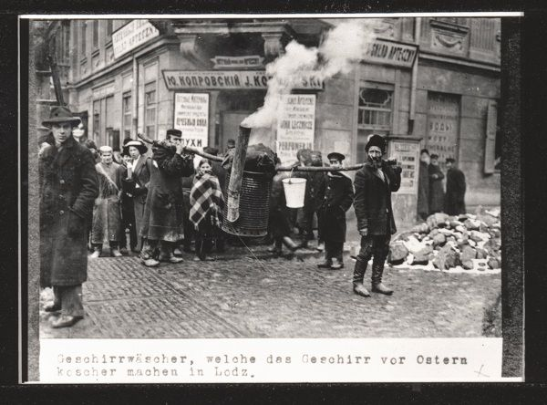 """""""Dish washers who wash dishes to make them kosher for Passover."""" Outside  J. Koprovsky's pharmacy. Lodz, WWI."""